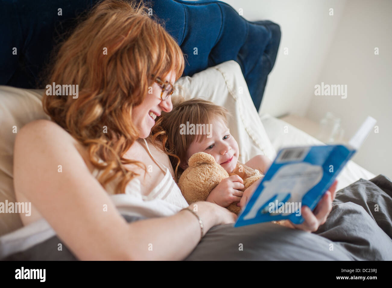 Mother and daughter reading book lying in bed - Stock Image