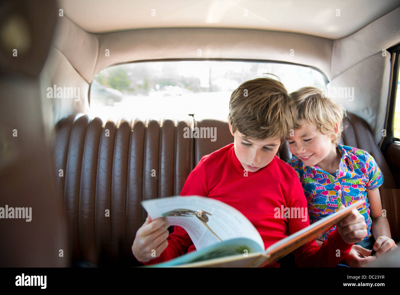Boys sitting in back of car reading book - Stock Image