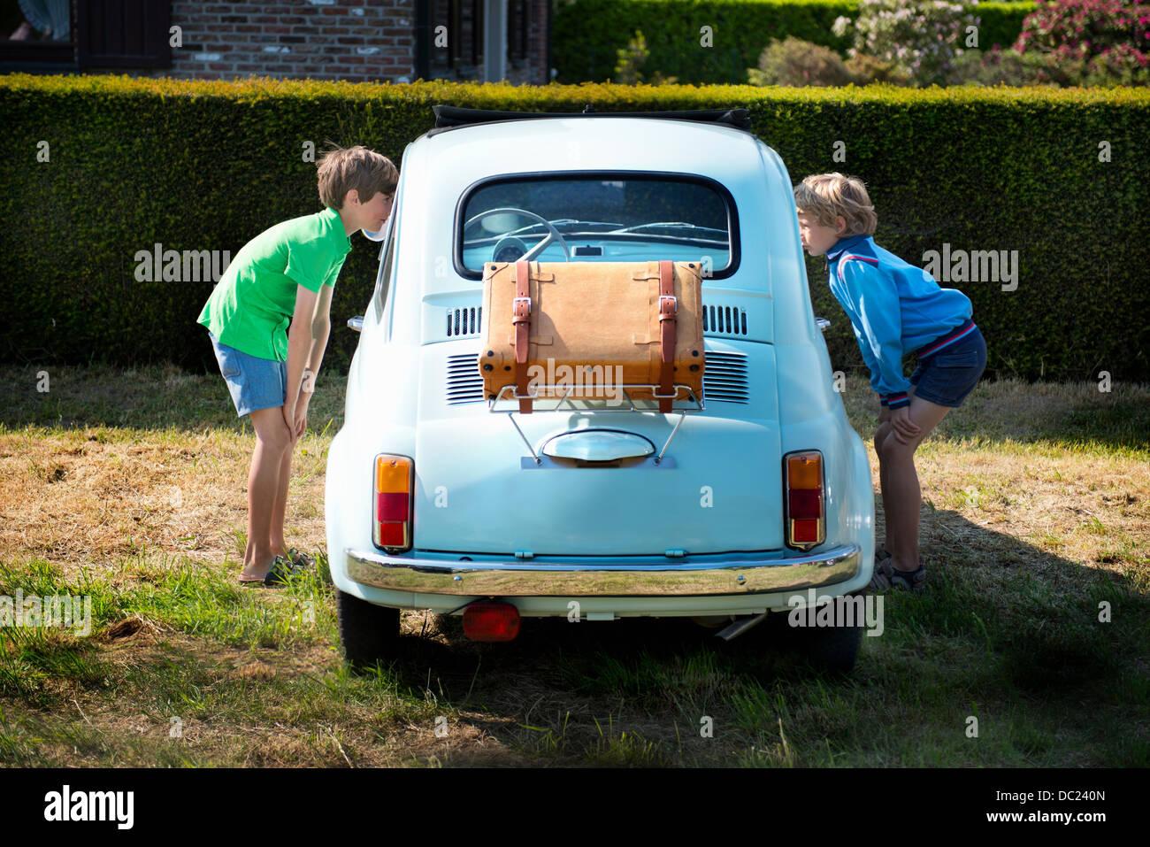 Boys looking through windows of vintage automobile - Stock Image