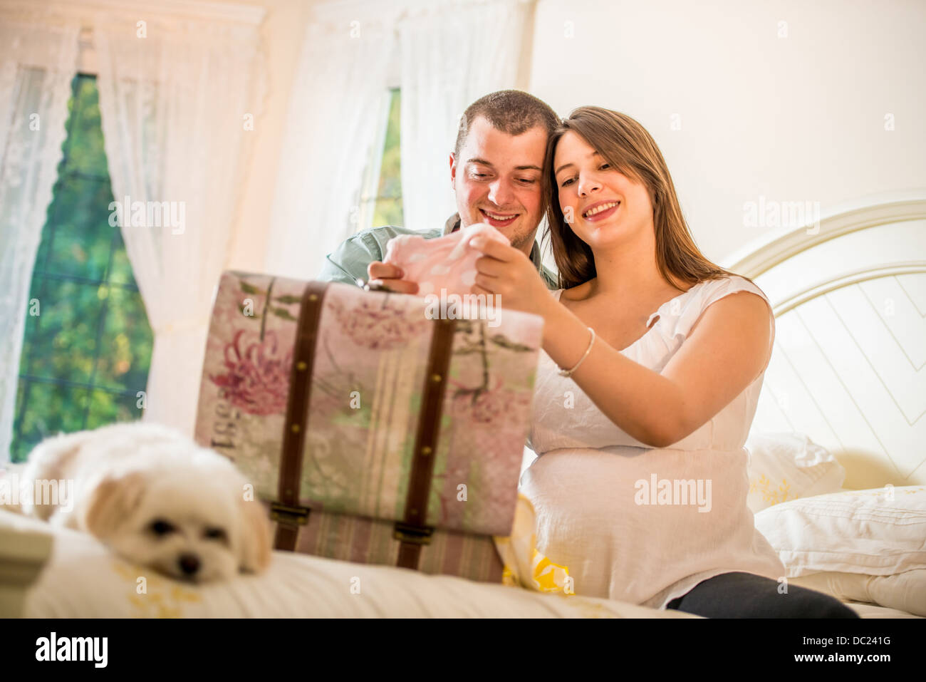 Couple looking through case of baby clothes - Stock Image