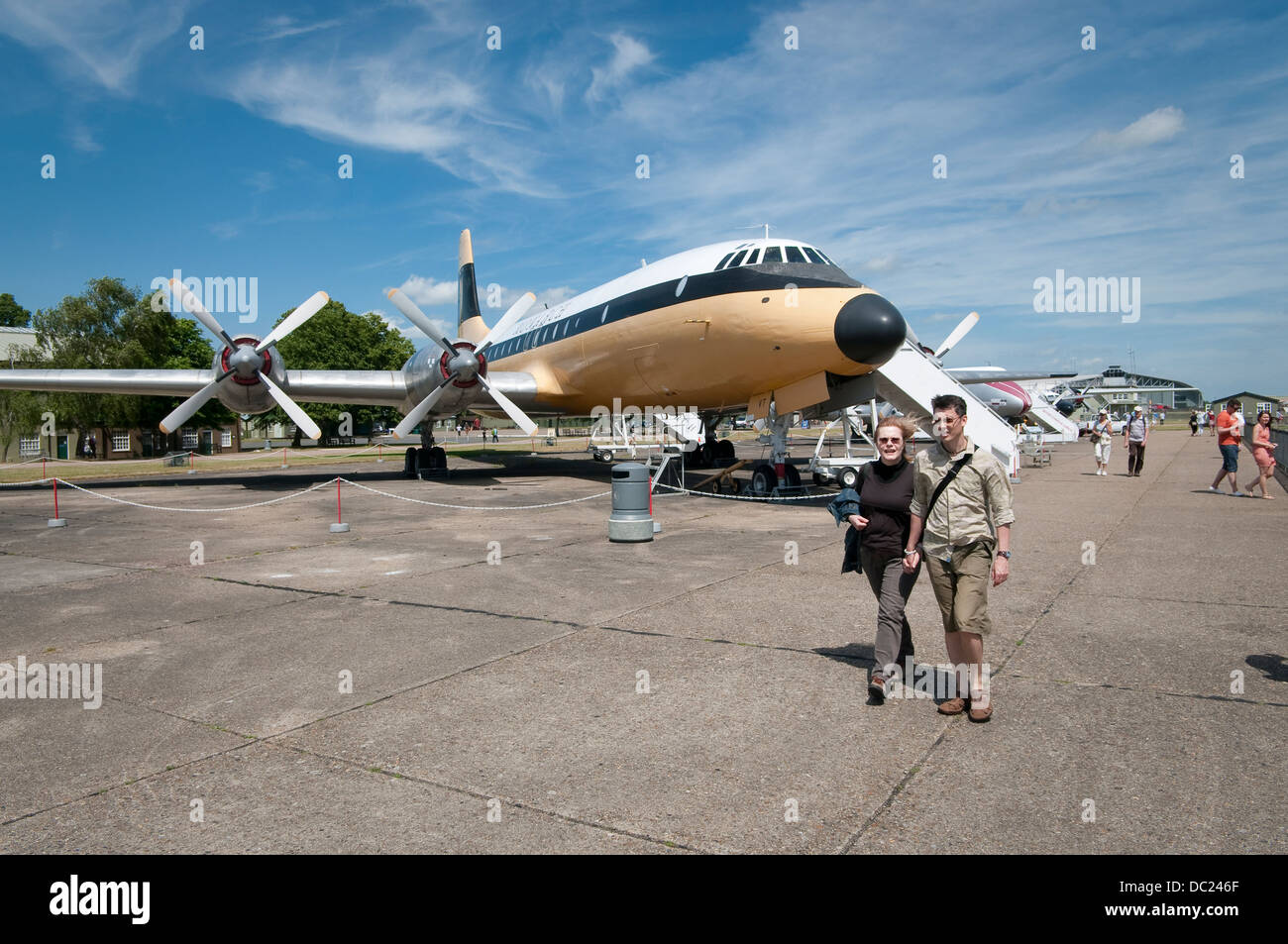 Visitors at Duxford Imperial War Museum. Couple walking along civil aircraft exposition. Bristol Britannia 312 aircraft. - Stock Image