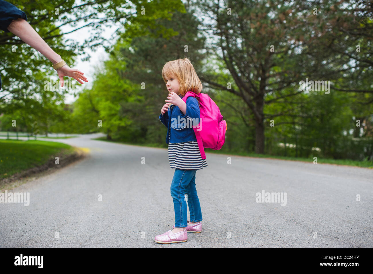 Mother reaching out to hold daughter's hand - Stock Image