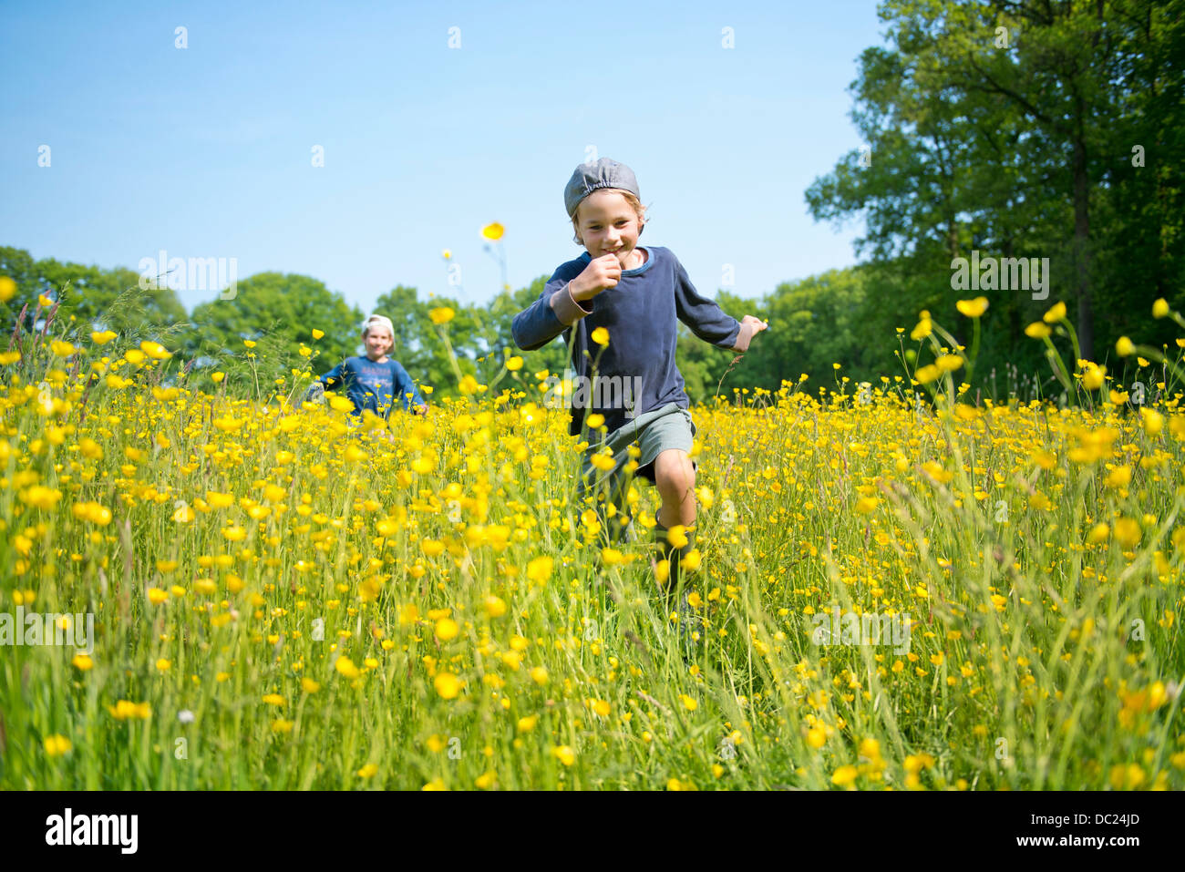 Brothers running through long grass and flowers - Stock Image