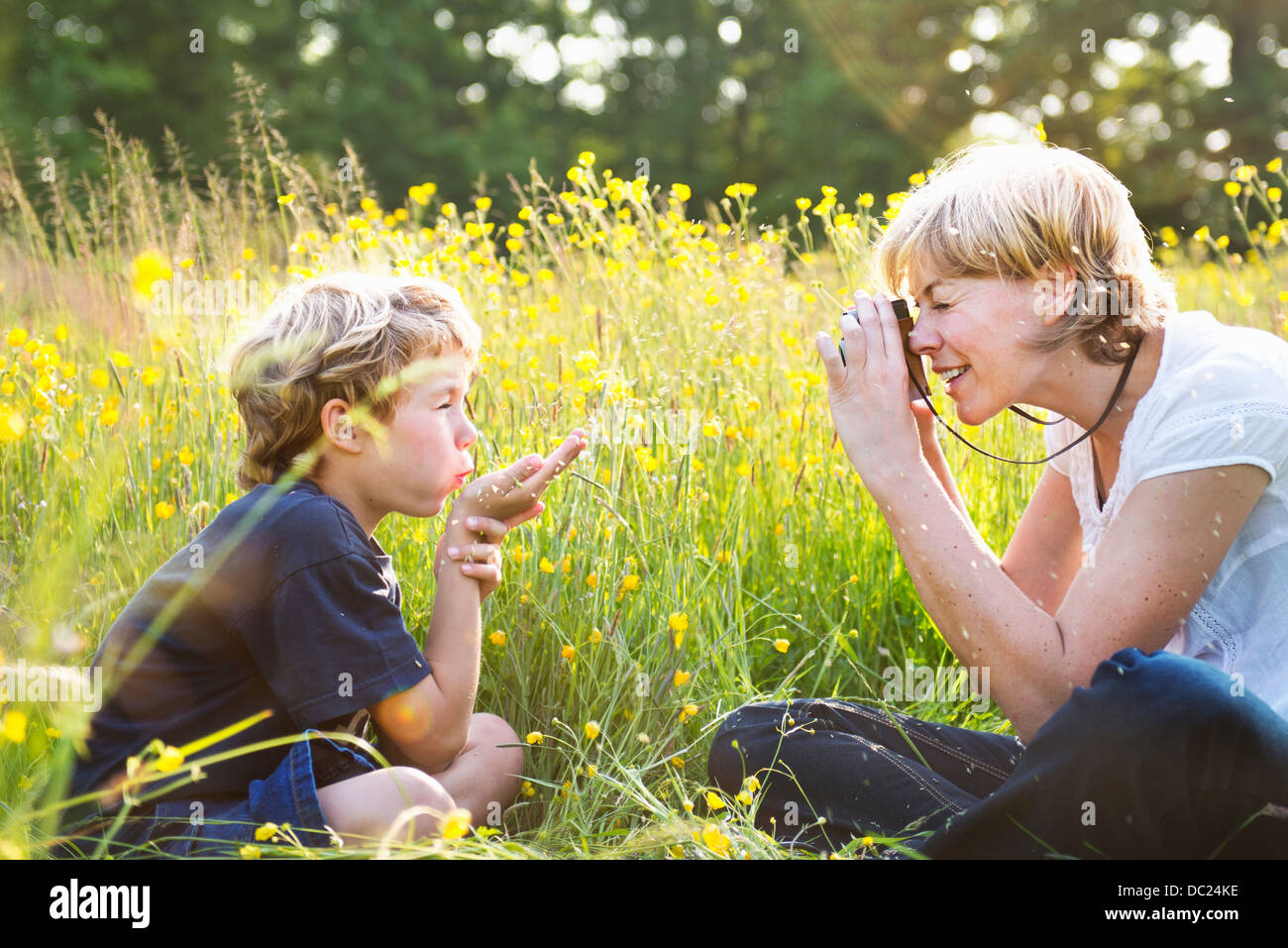 Woman taking photograph of boy blowing kiss - Stock Image