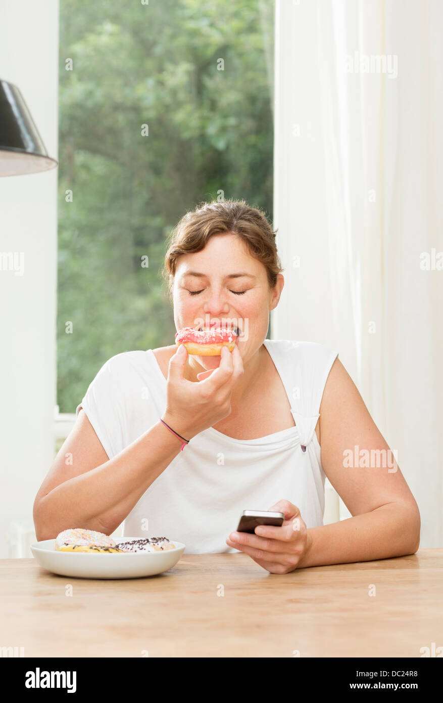 Woman sitting at table eating donut and using smartphone - Stock Image