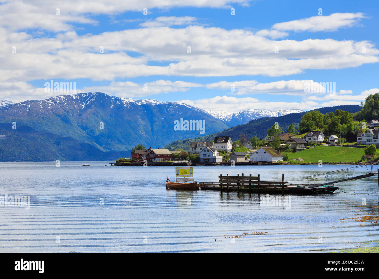 Snowcapped mountains across Hardangerfjorden in summer from coastal village of Øystese, Kvam, Hardanger, Hordaland, - Stock Image