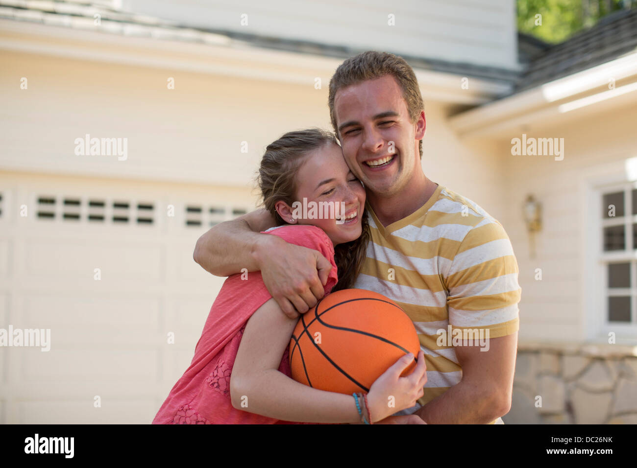 Brother with arm around sister holding basketball - Stock Image