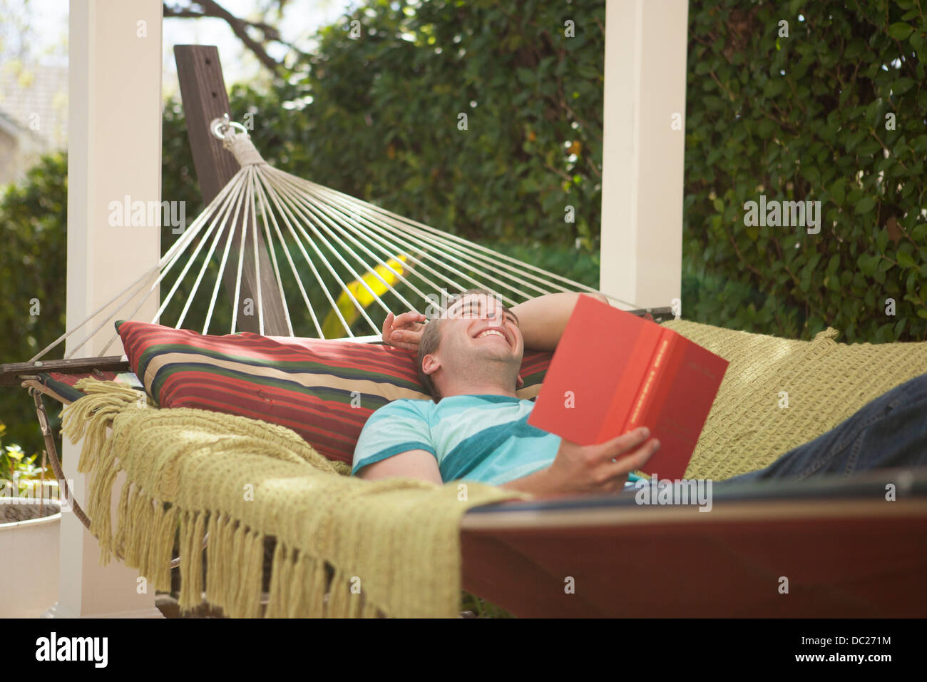 Young man reading book in hammock, laughing - Stock Image