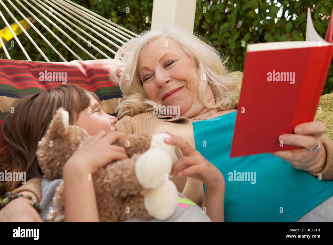 Grandmother and granddaughter reading book in hammock - Stock Image