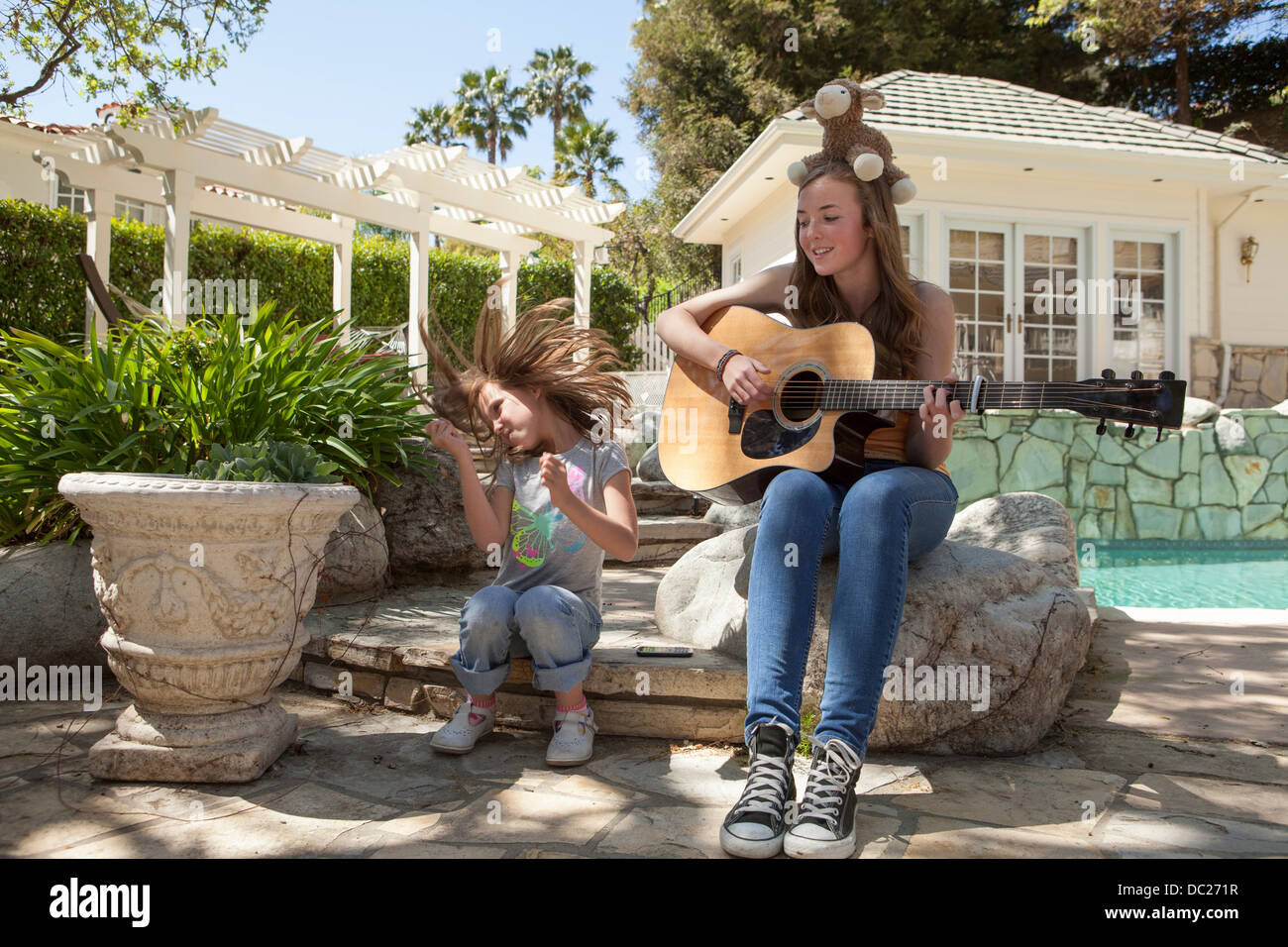 Girl with older sister playing guitar - Stock Image