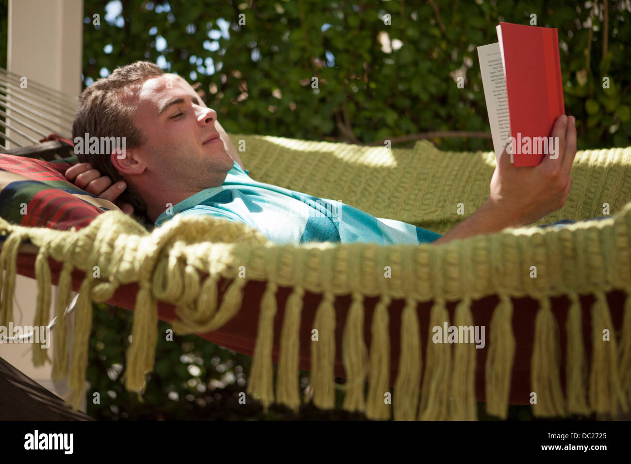 Young man reading book in hammock - Stock Image
