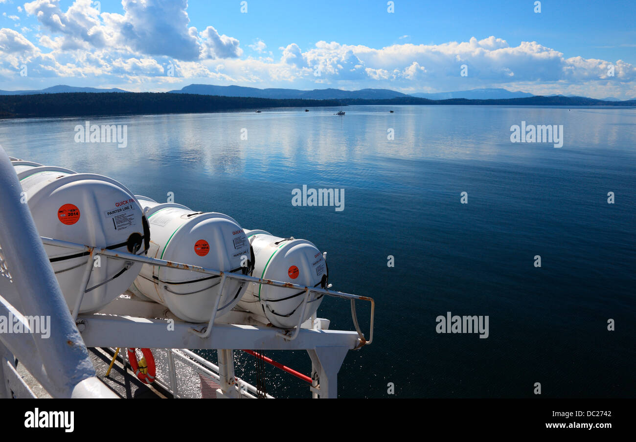 British Columbia Ferry boat in the Strait of Georgia on a sunny spring day. Gulf islands and clouds in background. - Stock Image