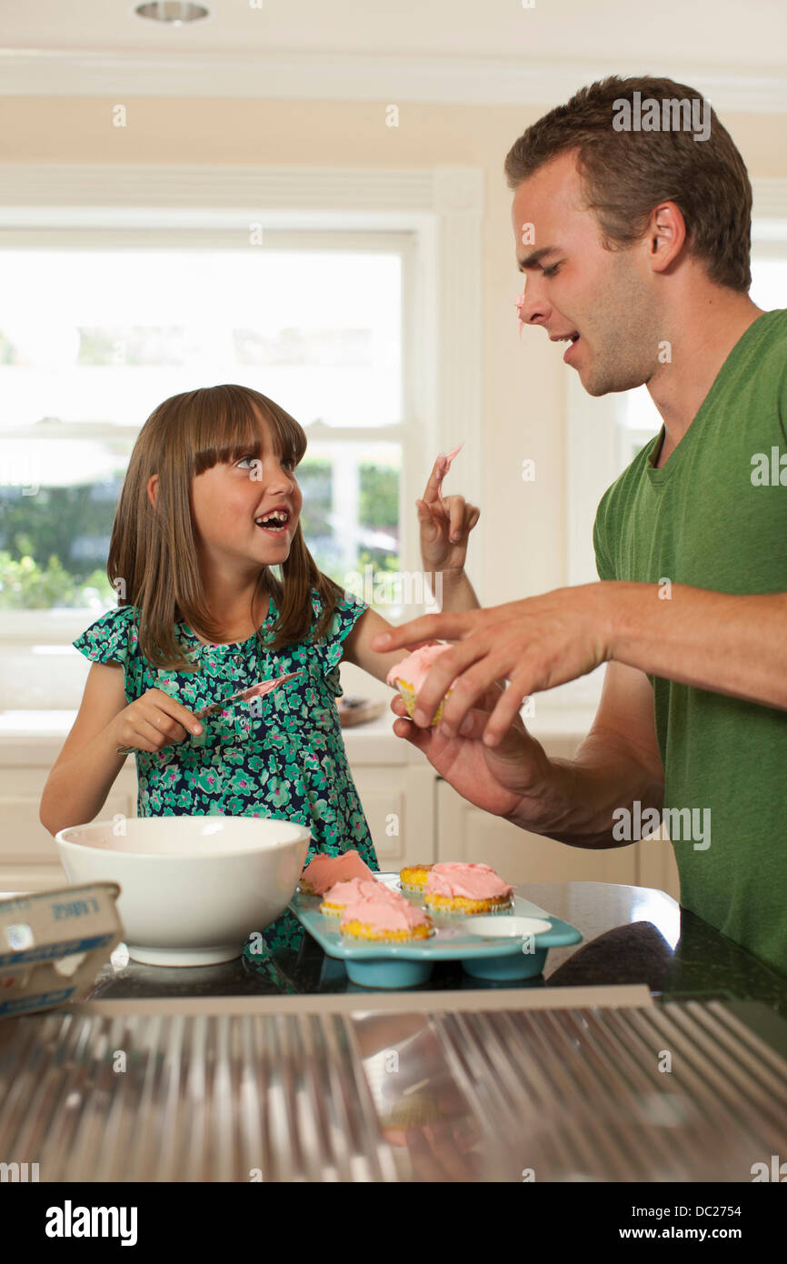 Young girl putting icing on older brother's nose - Stock Image