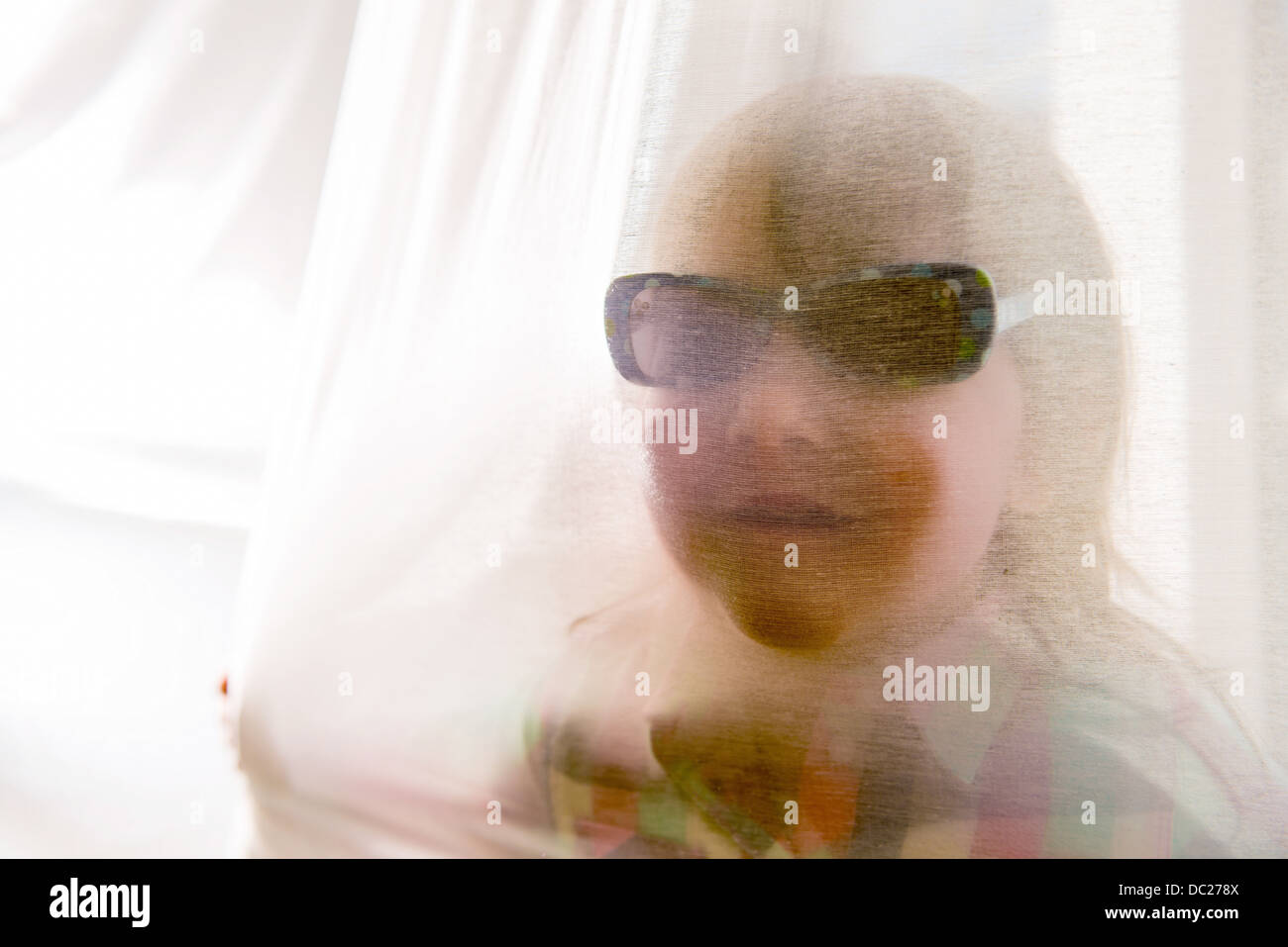 Girl looking through curtain wearing sunglasses - Stock Image
