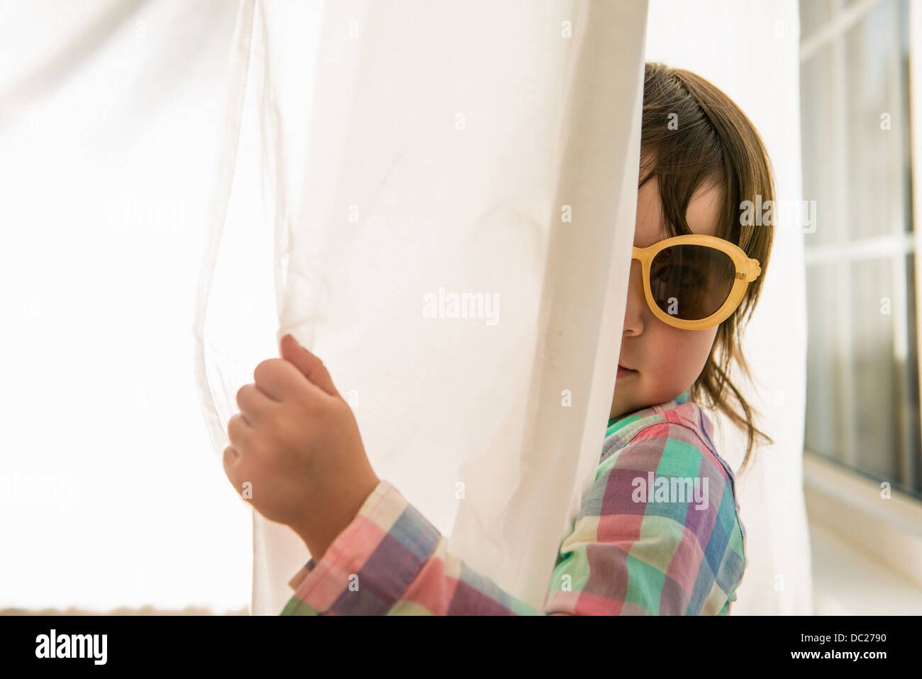 Girl peering round curtain wearing sunglasses - Stock Image