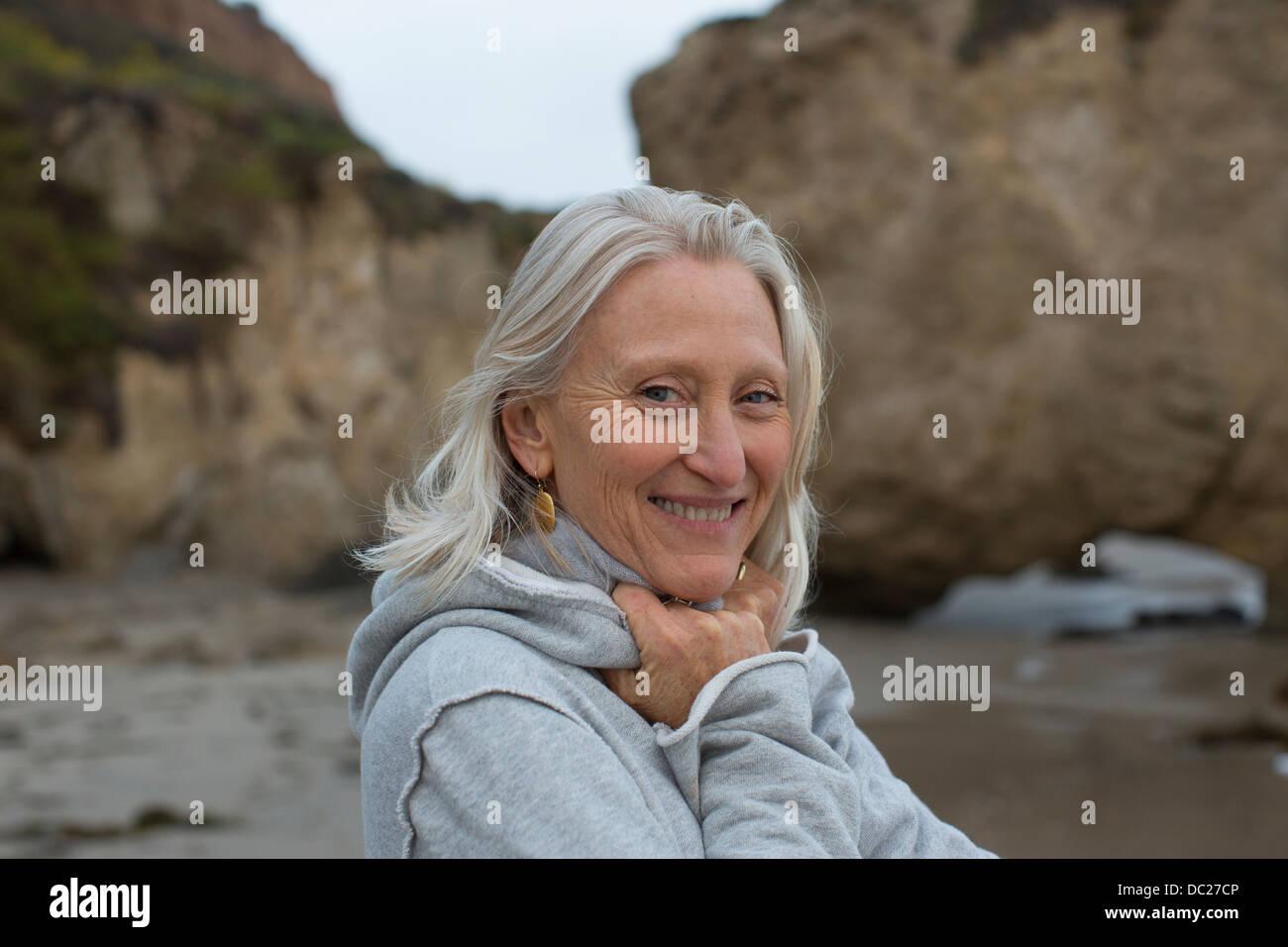 Mature woman wearing grey sweater on beach, smiling Stock Photo
