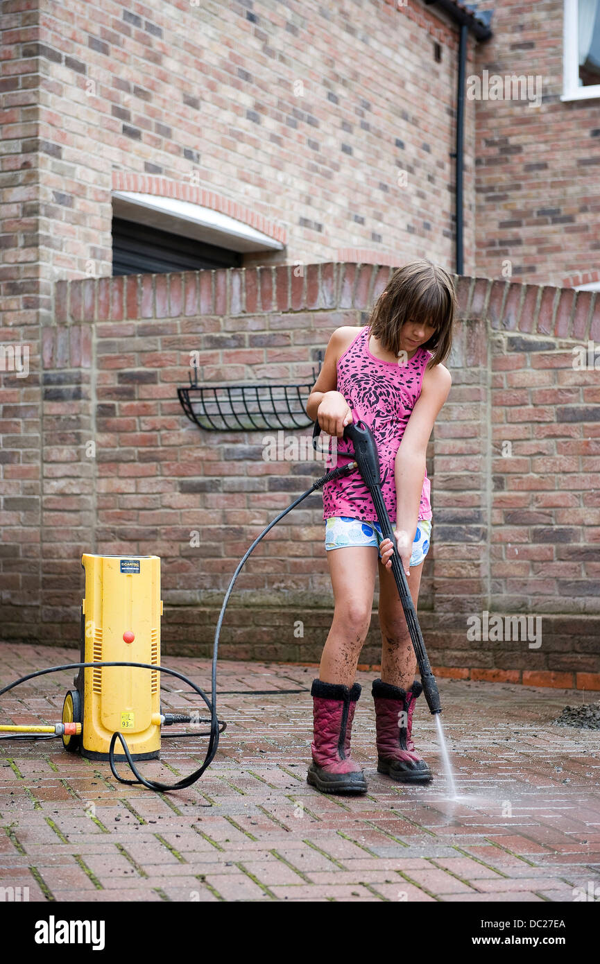A girl aged 10 uses a power washer to clean the family block pave drive drive at her home for pocket money. - Stock Image