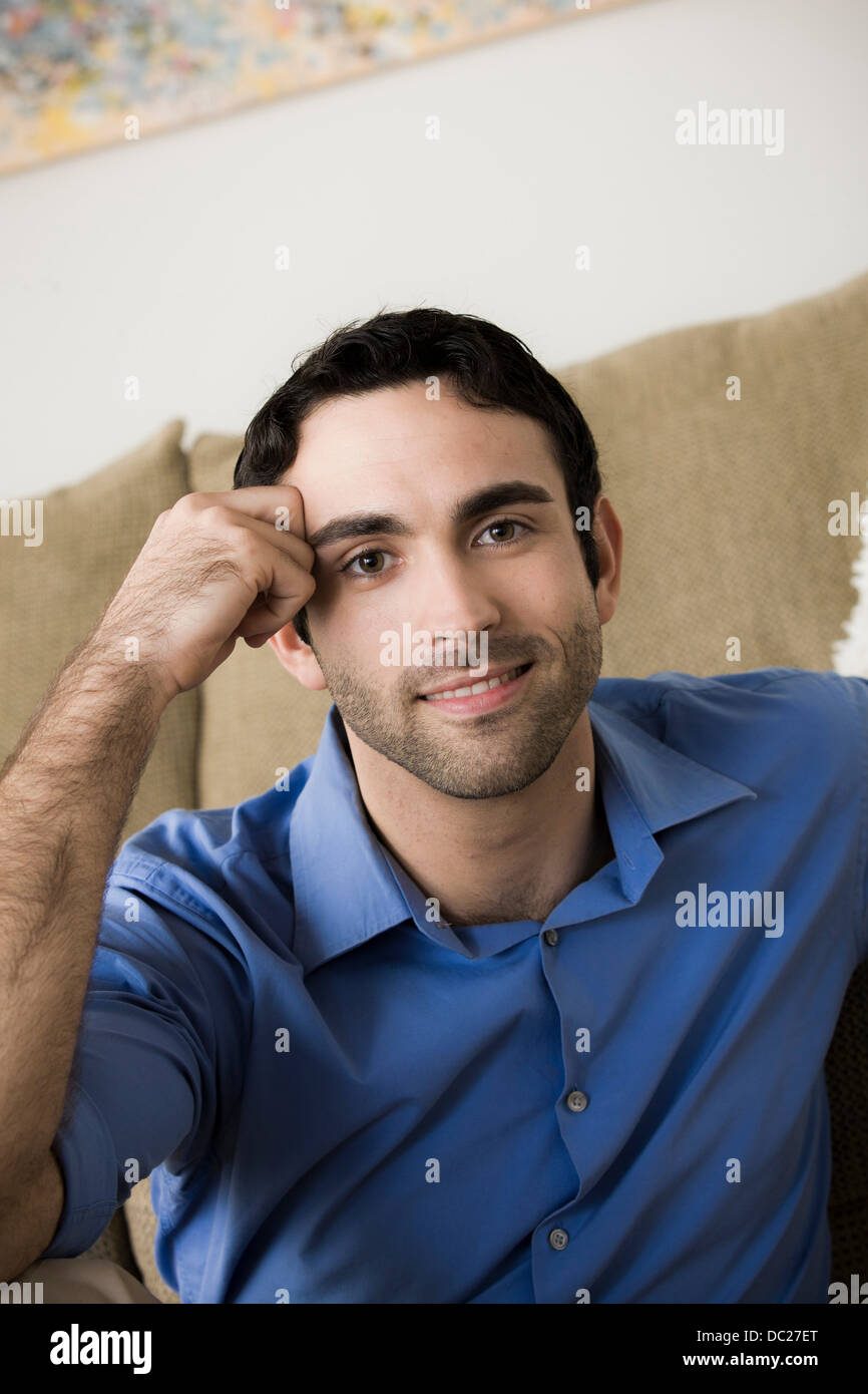 Portrait of young man leaning on elbow - Stock Image