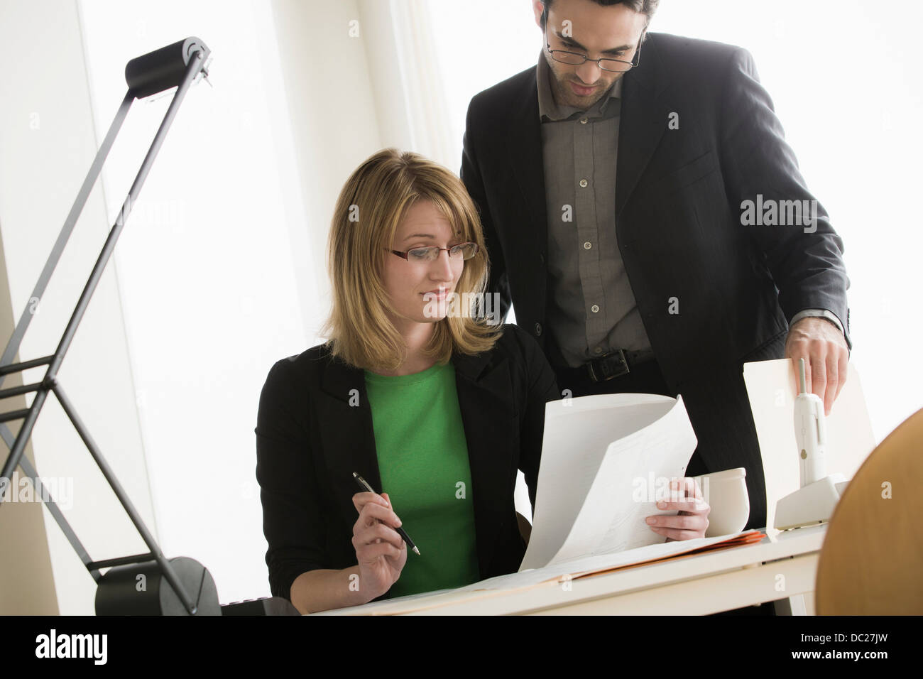 Young office workers looking through paperwork - Stock Image