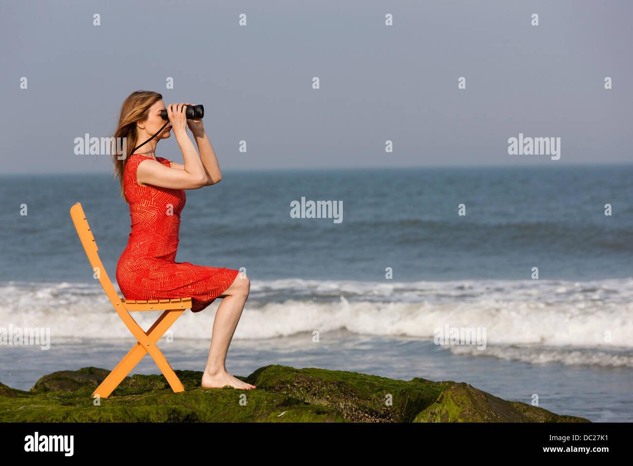 Mature woman sitting on chair on beach with binoculars - Stock Image