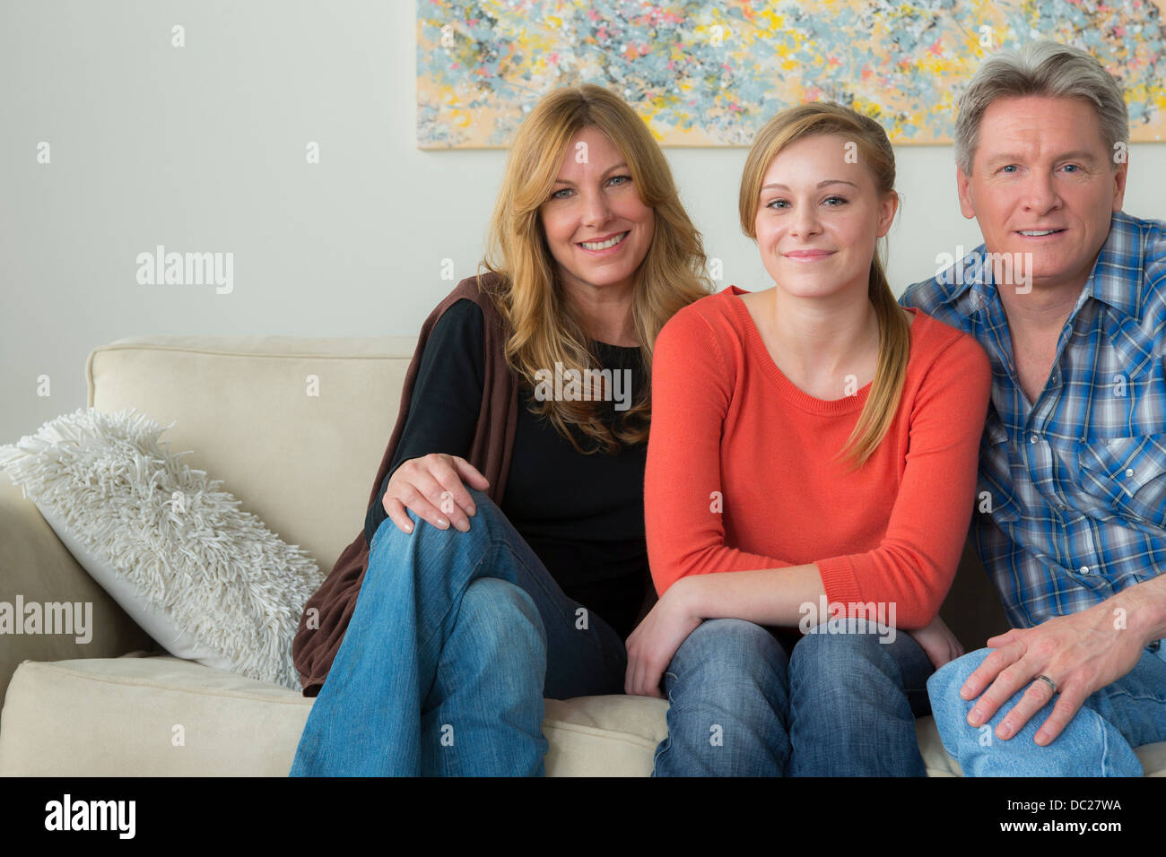 Portrait of mother and father with teenage daughter on sofa - Stock Image