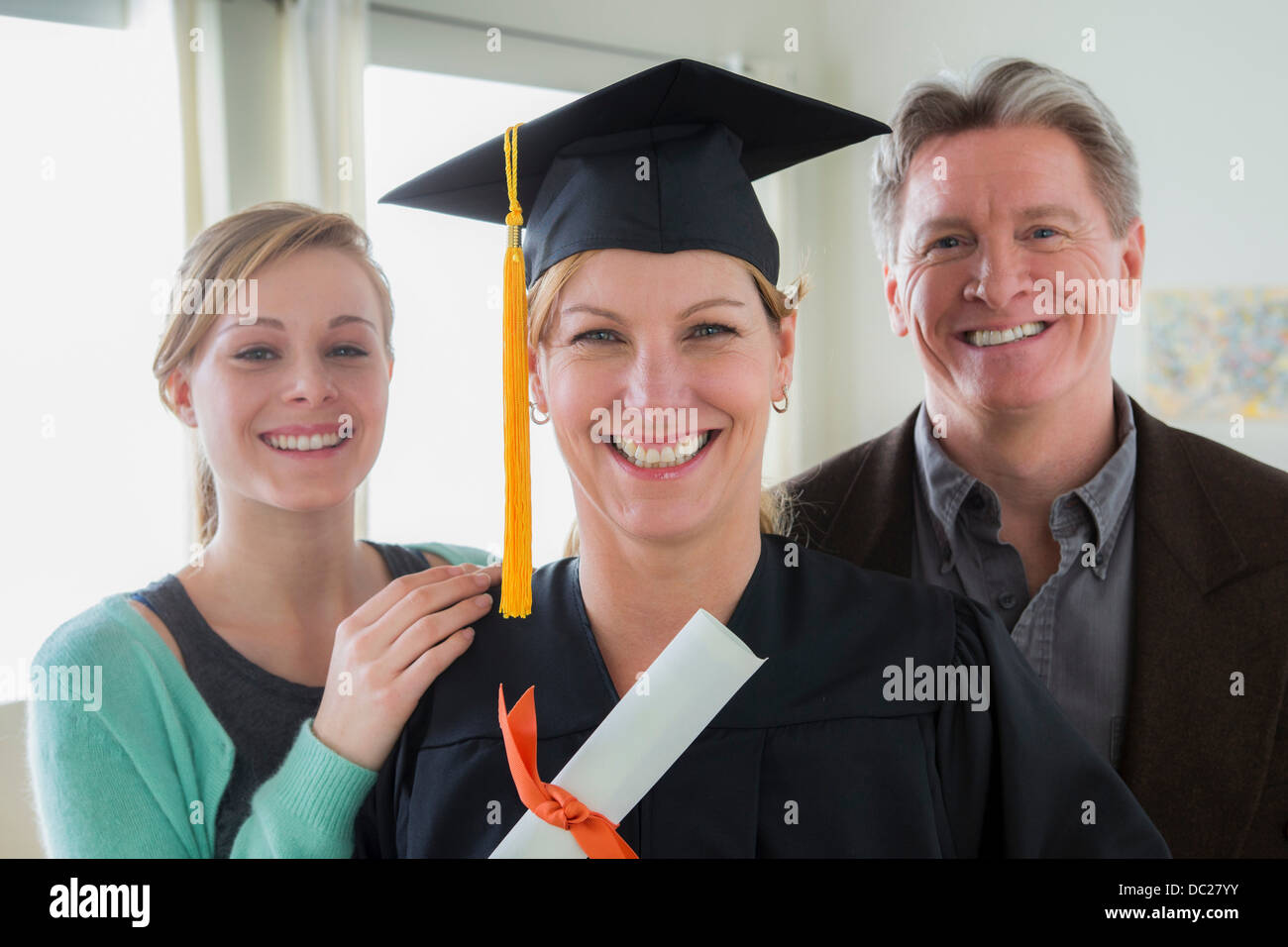 Mother wearing mortarboard with daughter and husband - Stock Image