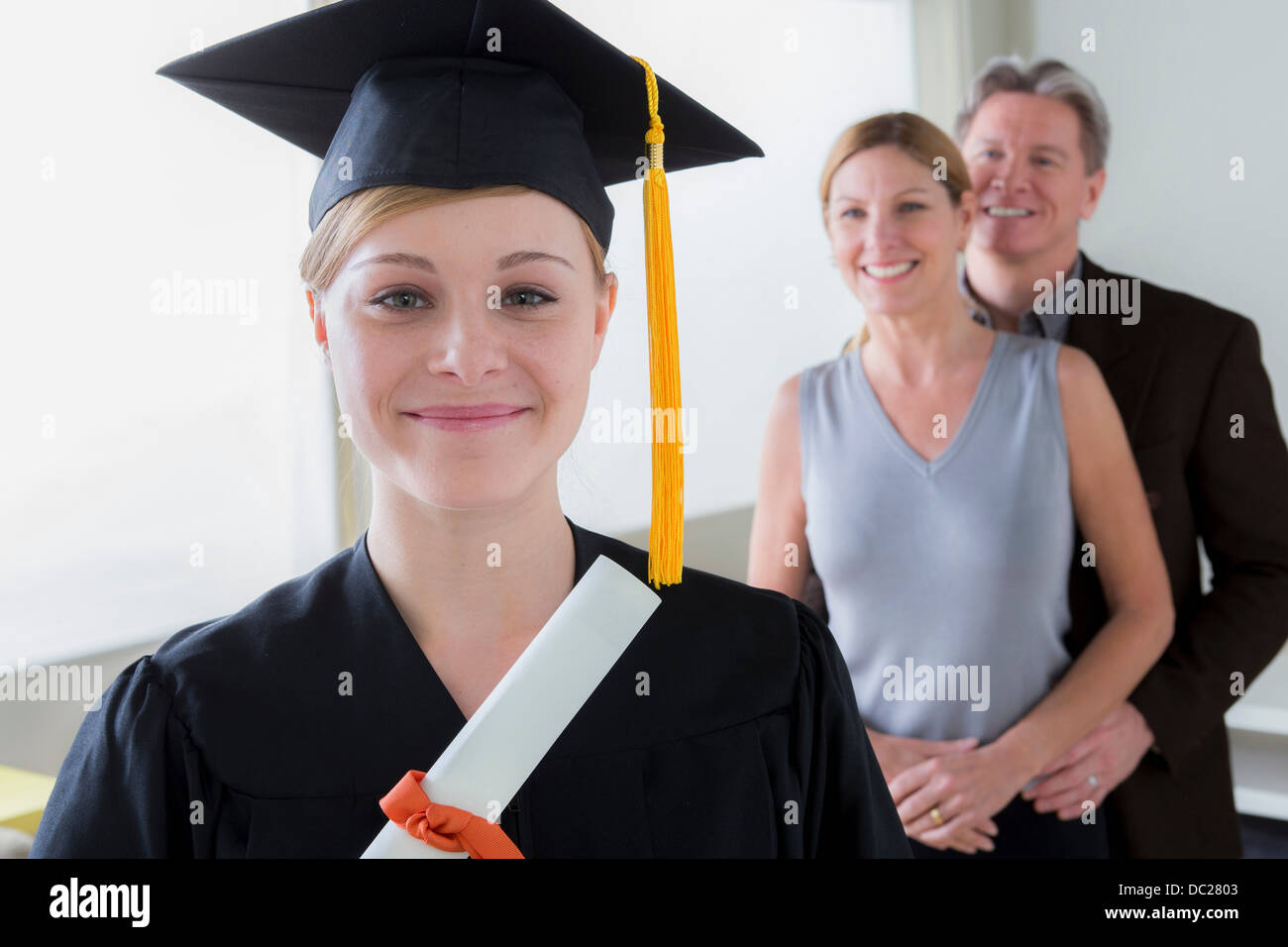 Teenage girl wearing mortarboard with parents in background Stock Photo