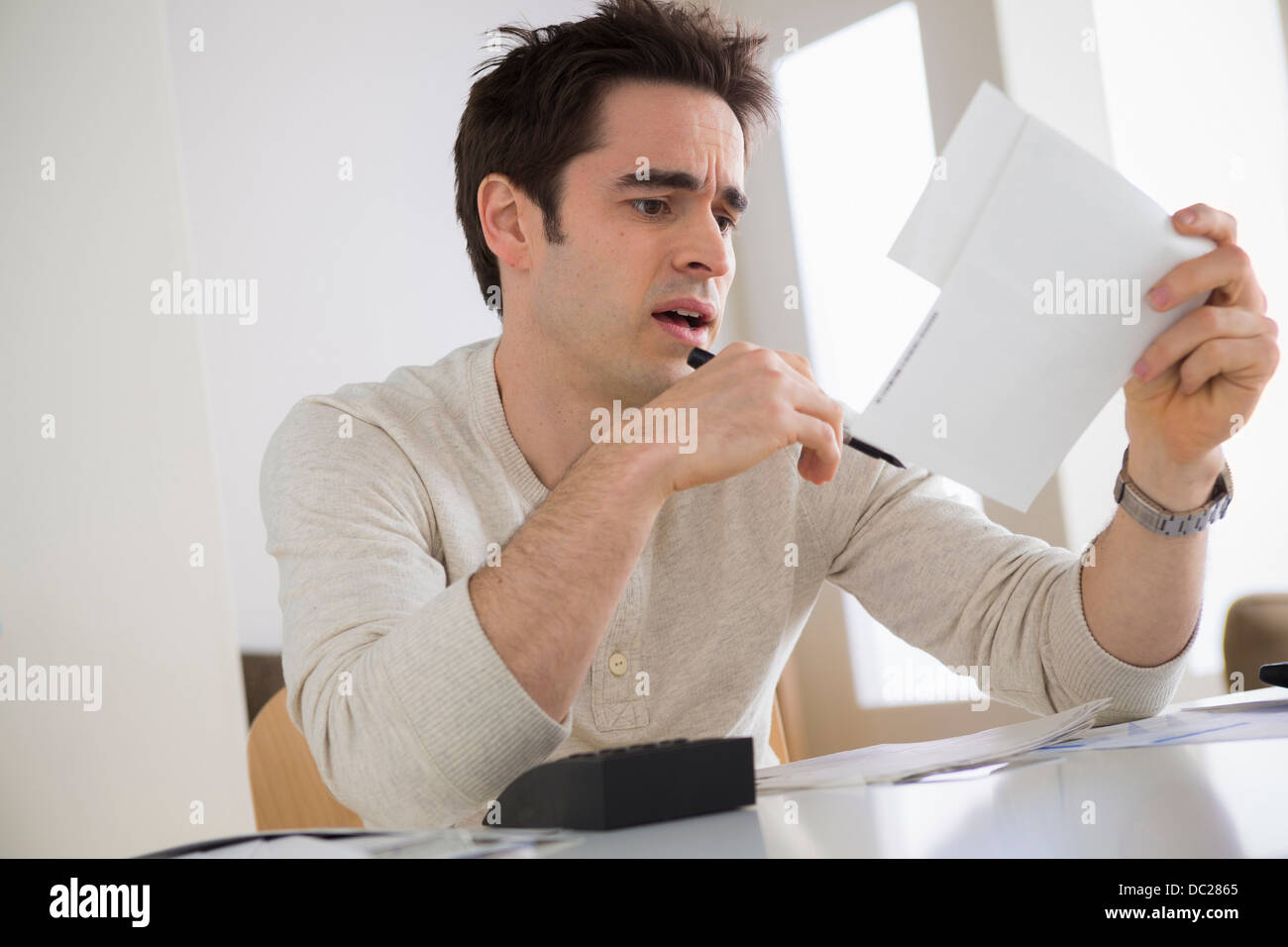 Worried looking man wearing holding document - Stock Image