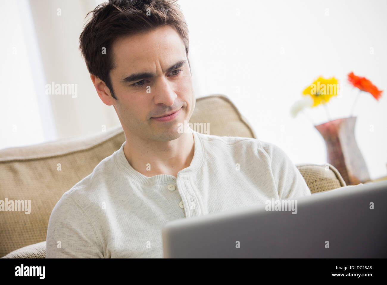 Mid adult man using laptop, frowning - Stock Image