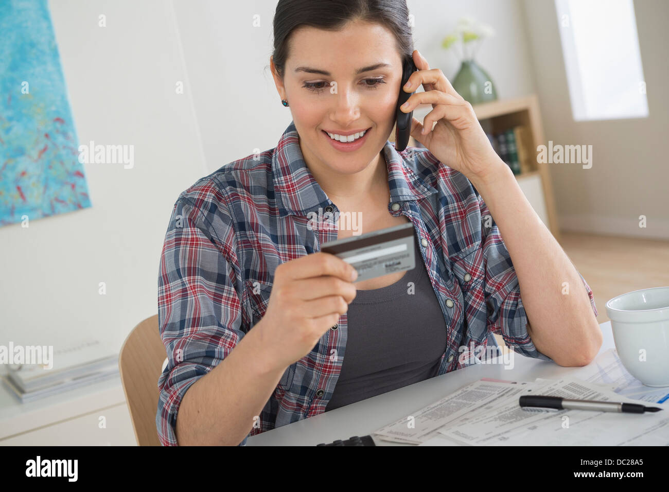 Young woman on cell phone with credit card - Stock Image