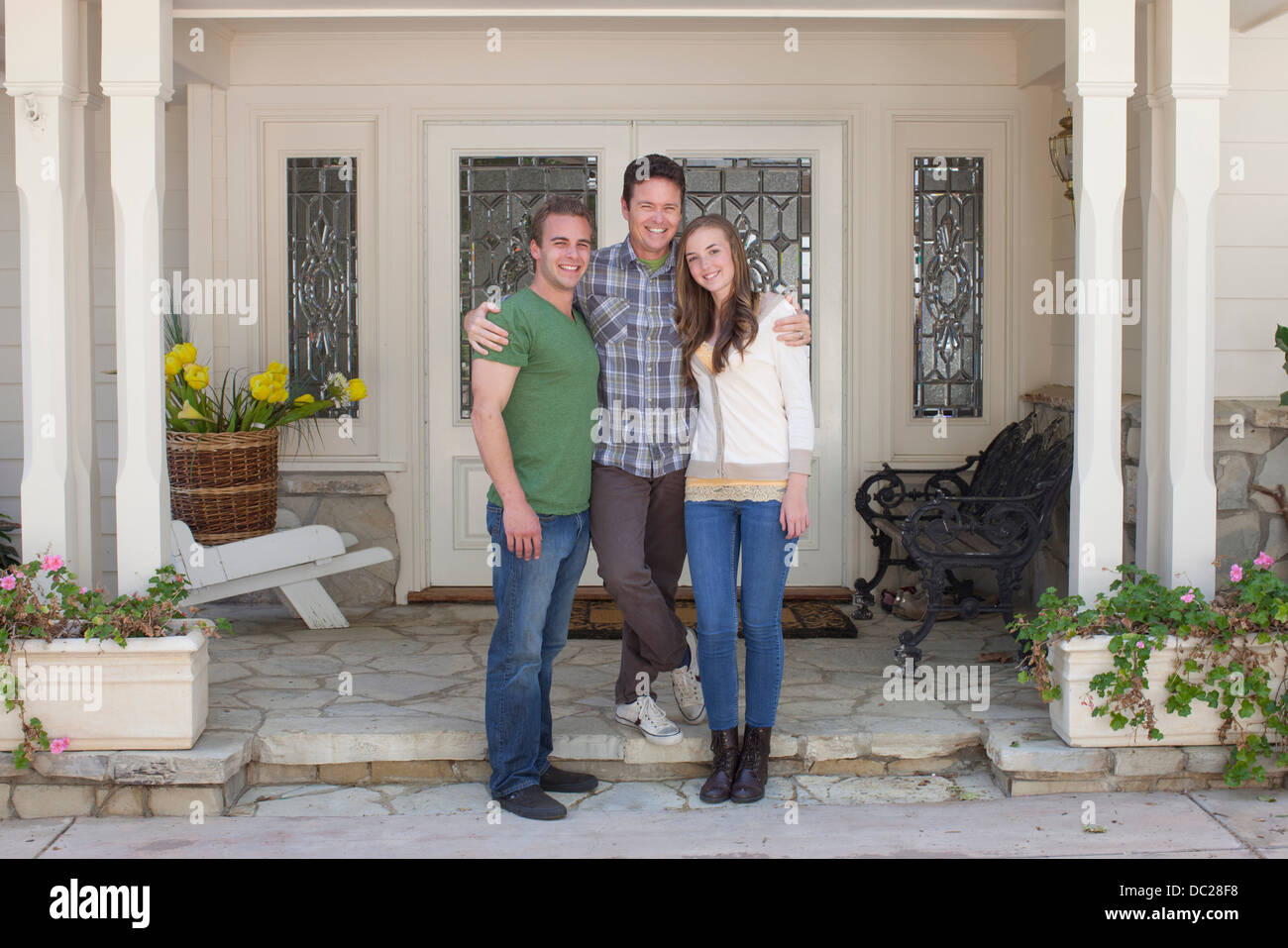 Portrait of father with adult offspring standing outside house - Stock Image