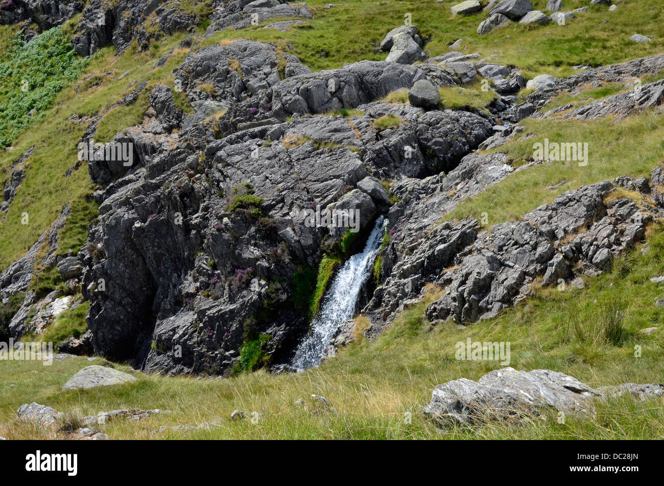 Waterfall and crag, Levers Beck in Copper Mines Valley Coniston, Lake District National Park. - Stock Image