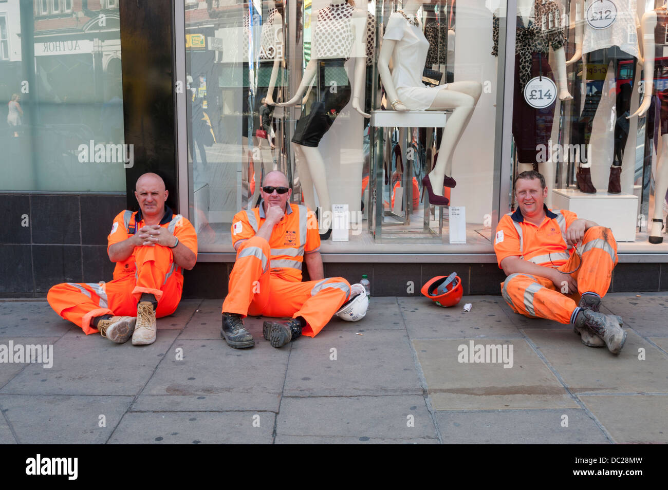 Three workmen in orange Hi Vis clothing take a break outside a shop in London UK - Stock Image