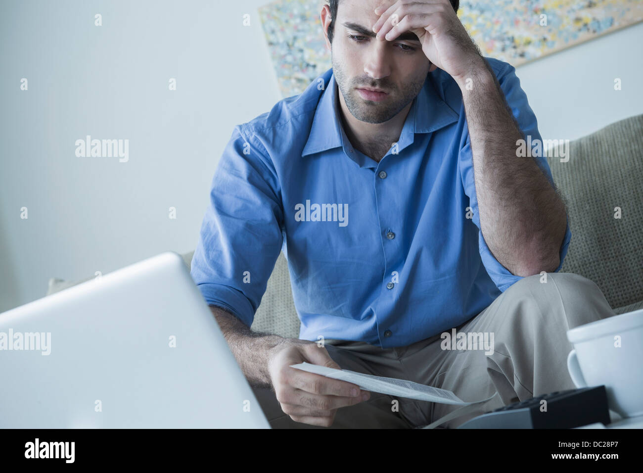Worried man with hand on head holding bills - Stock Image
