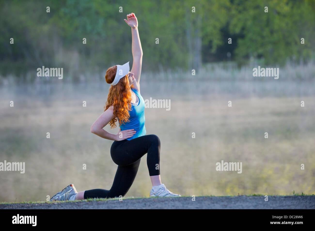 Teenage girl in sportswear stretching - Stock Image