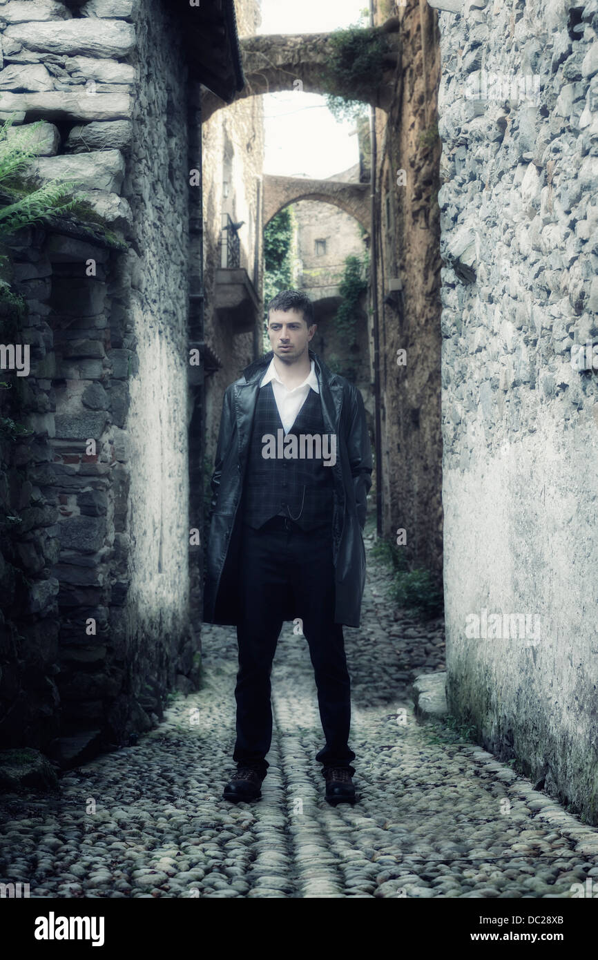a man in a black leather jacket is standing in an old, narrow alley - Stock Image