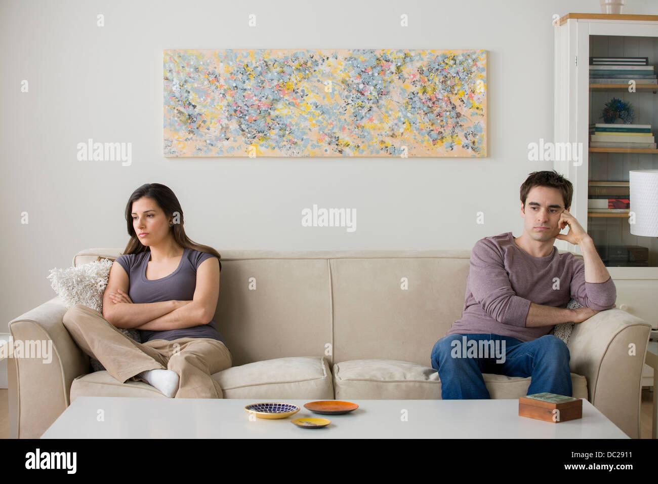 Couple sitting on sofa ignoring each other Stock Photo
