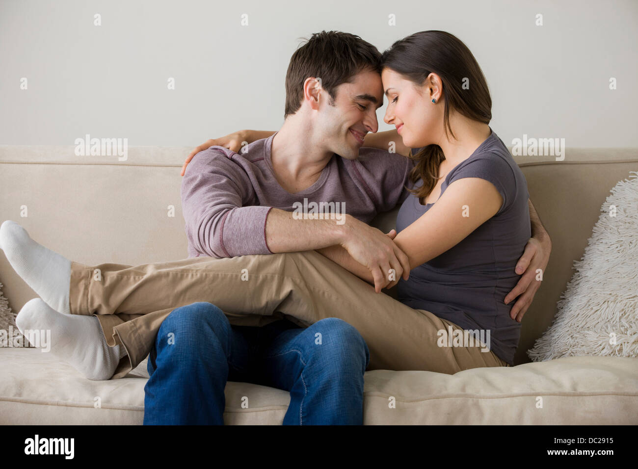 Couple on sofa, woman sitting on man's lap - Stock Image