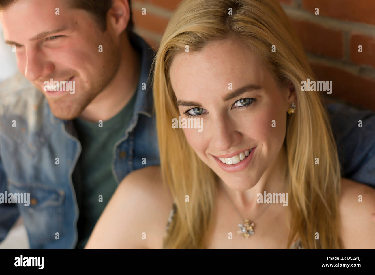 Portrait of couple, focus on young woman smiling - Stock Image