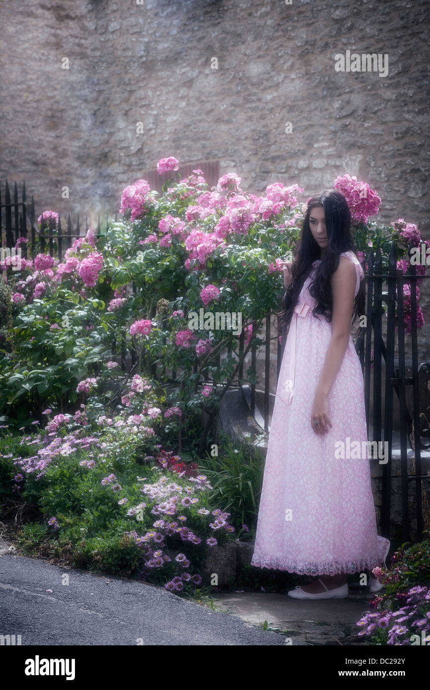 a beautiful woman with long black hair standing in a vintage pink dress in front of a gate with flowers - Stock Image