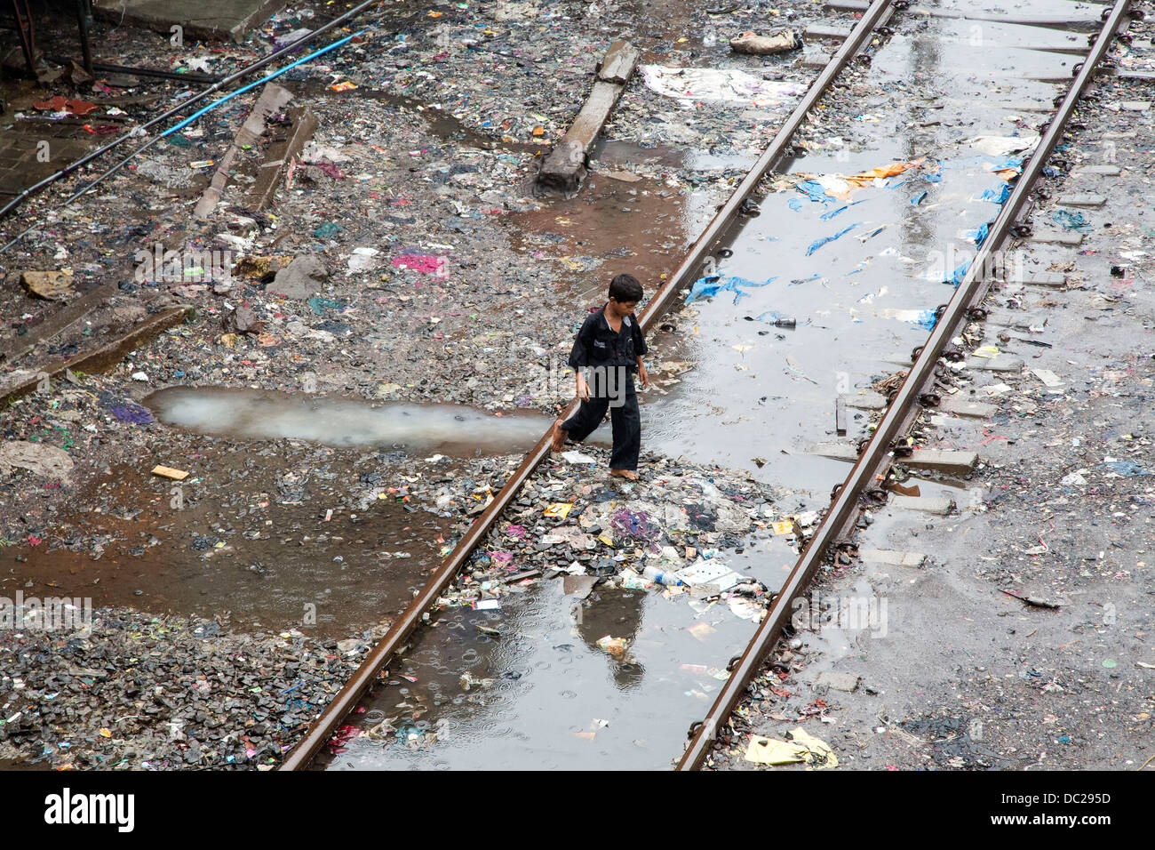 Boy walks through puddles and filth of Bandra slum area with train tracks running through - Stock Image