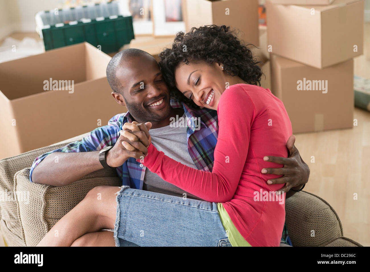 Mid adult couple on armchair in new home Stock Photo