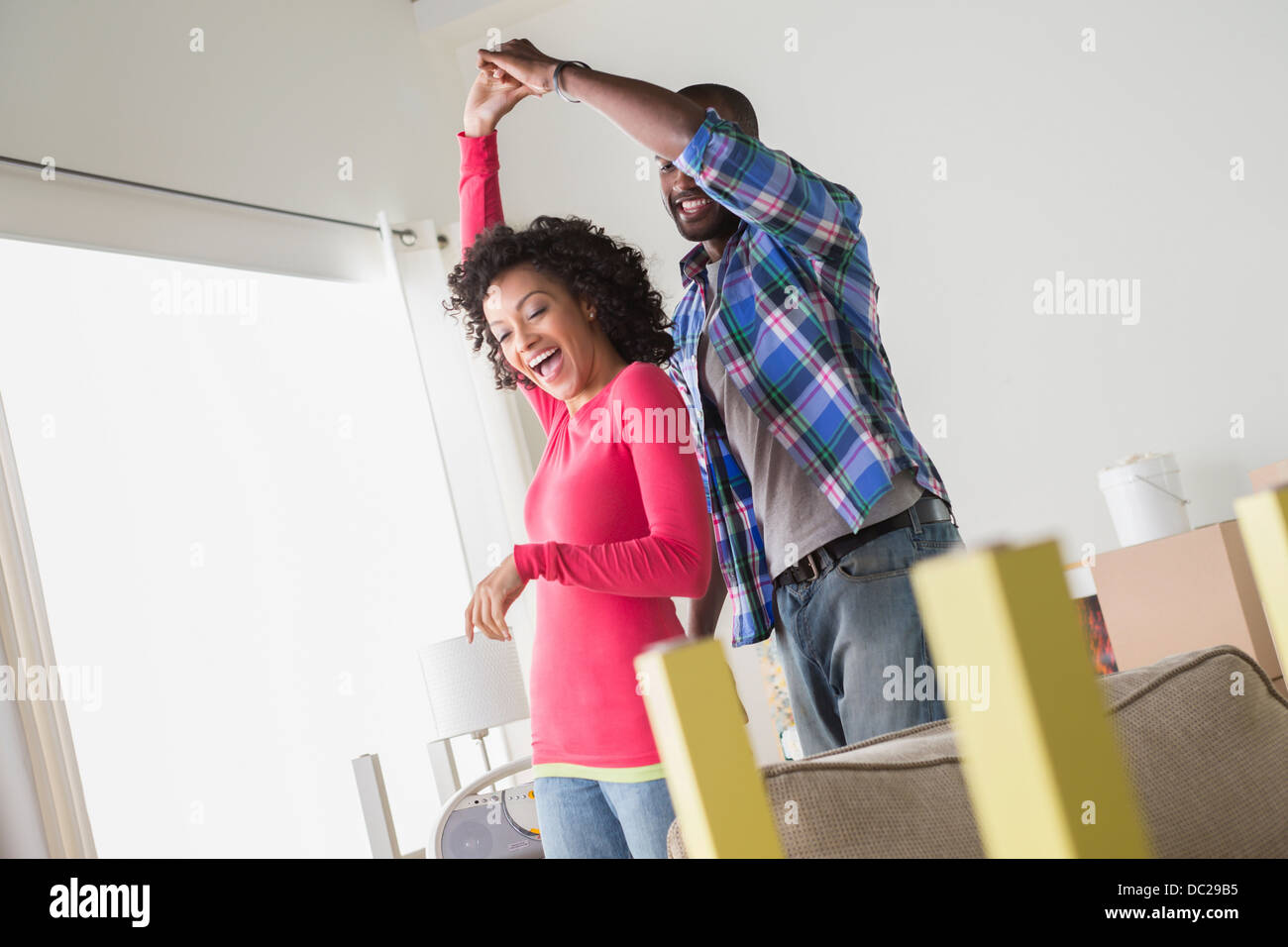 Mid adult couple dancing in new home - Stock Image