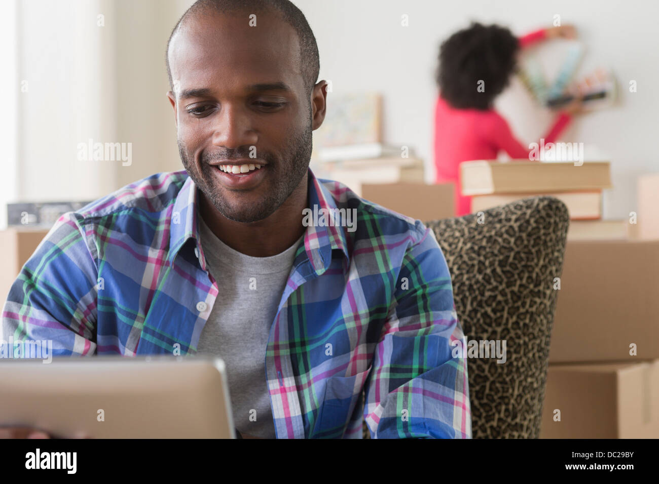 Mid adult man using electronic reader - Stock Image