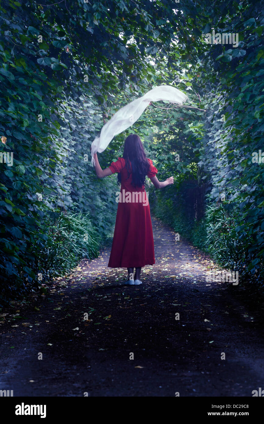 a woman in a red dress is walking through the woods with a white shawl - Stock Image