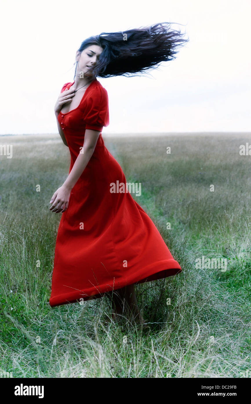 a woman in a red dress is dancing on a field - Stock Image