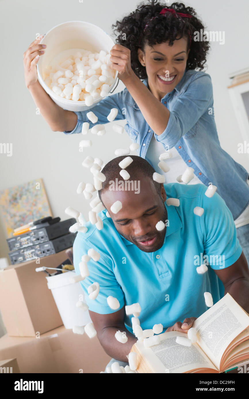 Mid adult woman pouring polystyrene over man's head - Stock Image