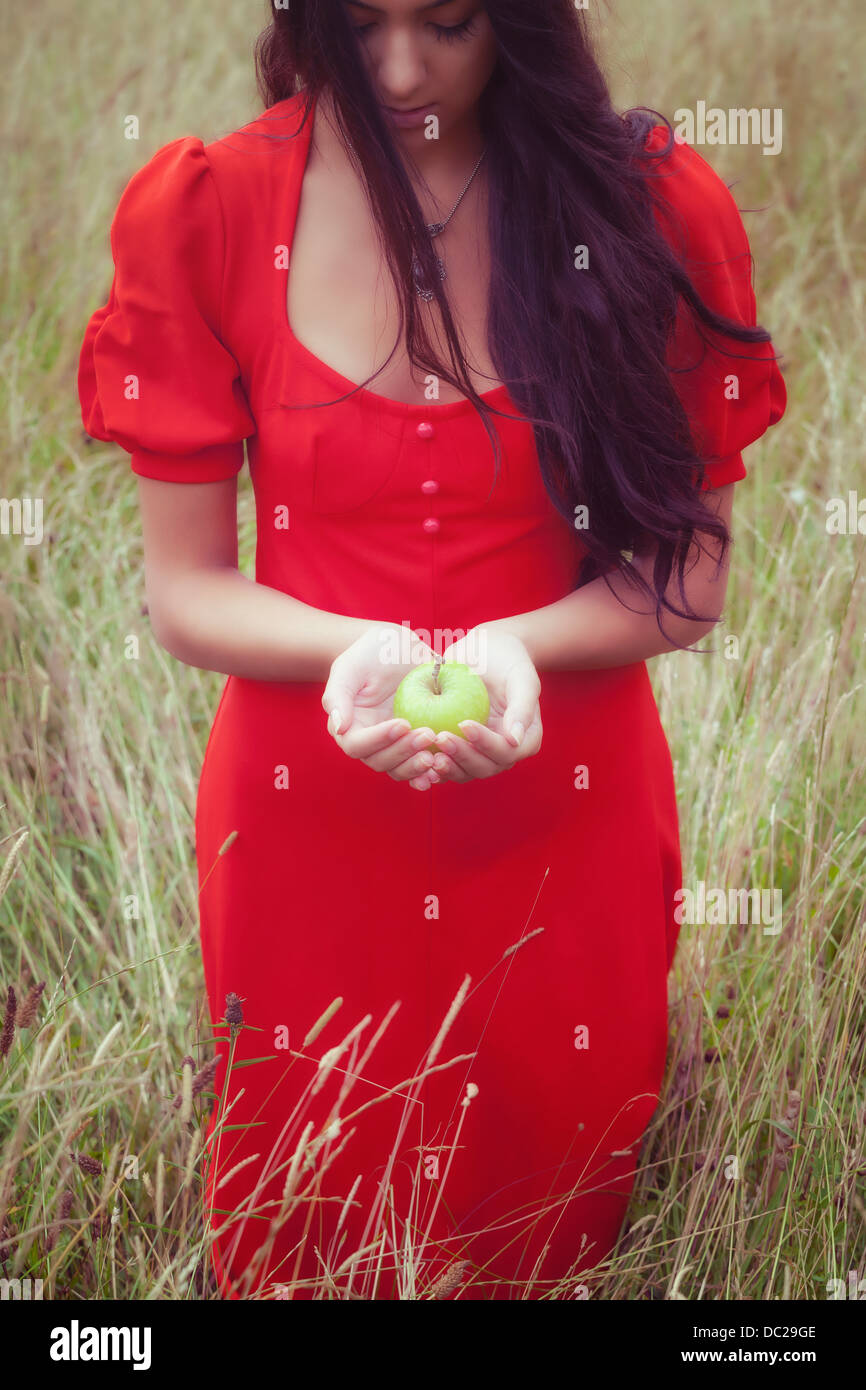 a woman in a red dress, holding a green apple - Stock Image