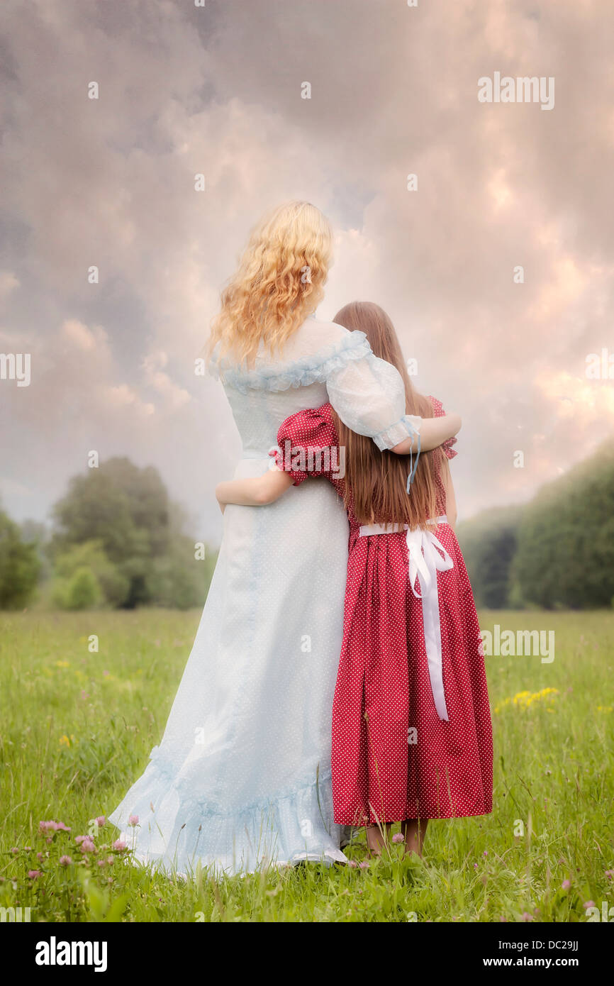 two girls in vintage dresses standing on a meadow, embracing each other - Stock Image