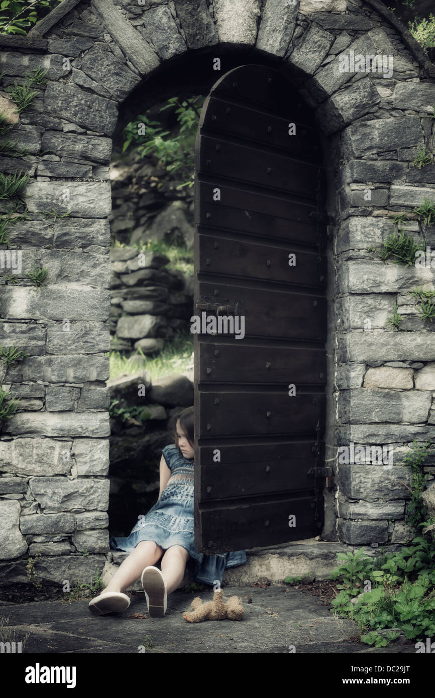 a sad, young girl is sitting in an old door with a teddy bear - Stock Image